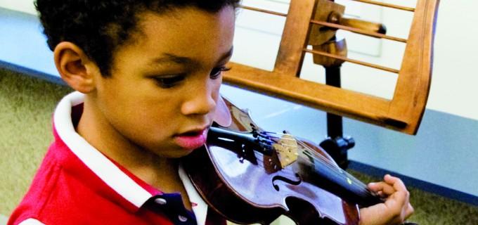 niño tocando el violín en clases de música clásica